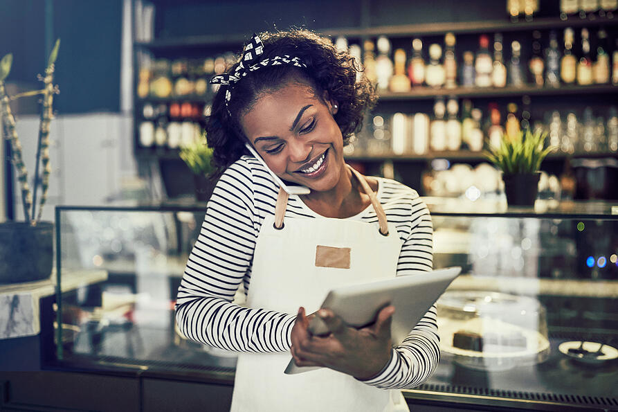 Happy barista chatting with a customer on the phone.