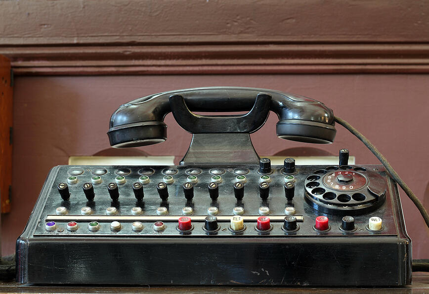 Outdated telephone with switches and rotary dial.