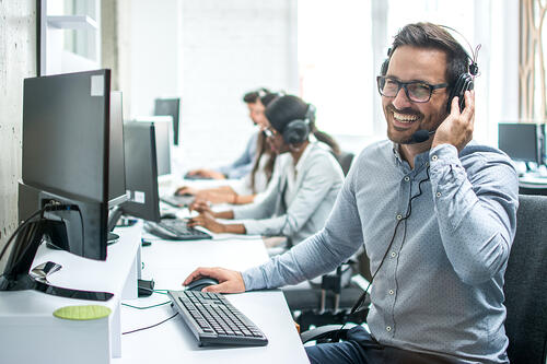 Call center employees taking calls on headsets.