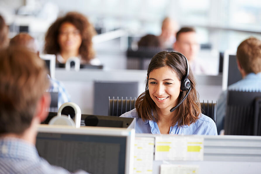 Woman in a call center speaking to a customer on a headset to keep her hands free.