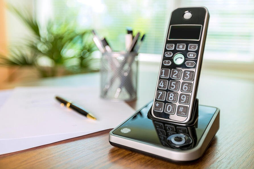 Cordless phone on a desk.