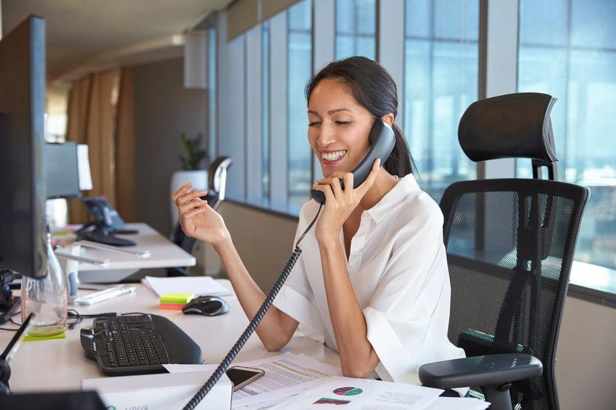 Businesswoman talking on a desk phone in an office.