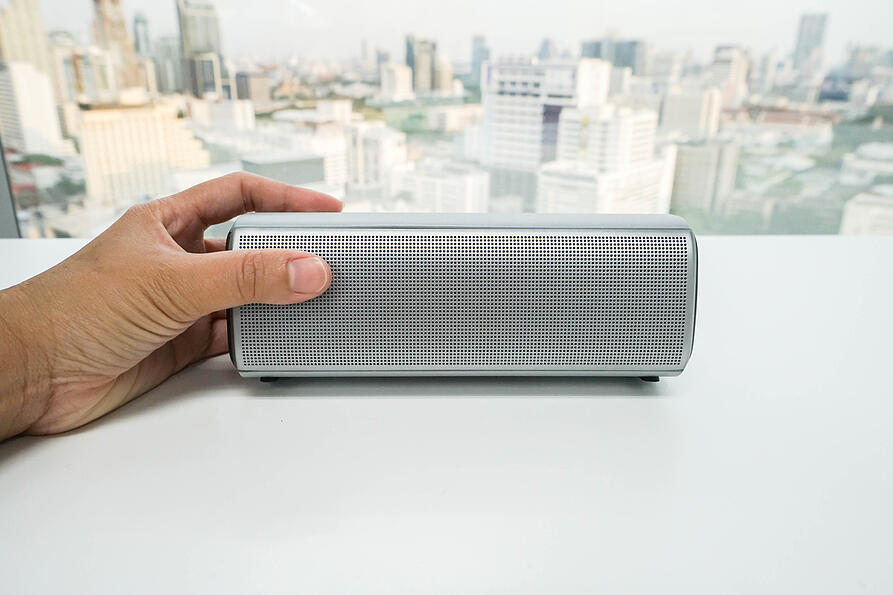Hand holding a small bluetooth speaker.