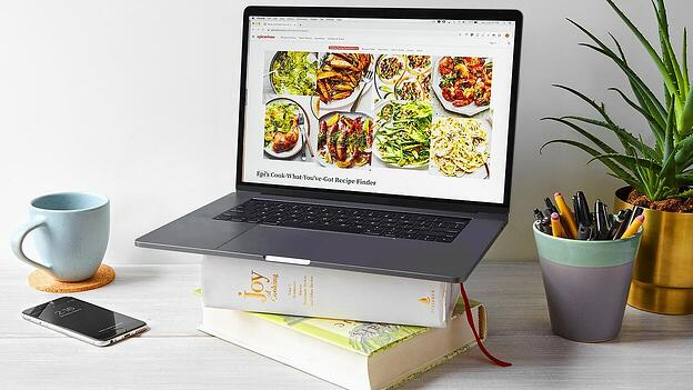 Image from Epicurious blog with a laptop on a stack of cookbooks.