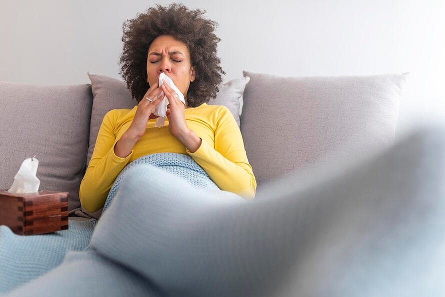 Sick woman on. couch sneezing into a tissue.