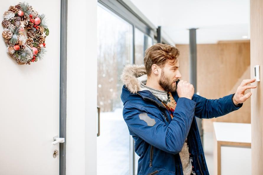 Man in fur parka adjusting wall thermostat.