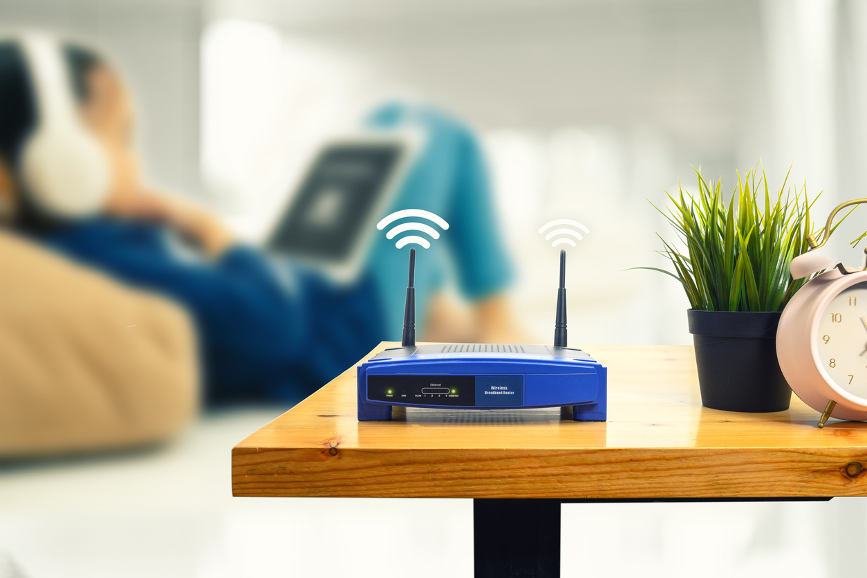 Router with WiFi signal above antennae on side table as someone watches an iPad in the background.