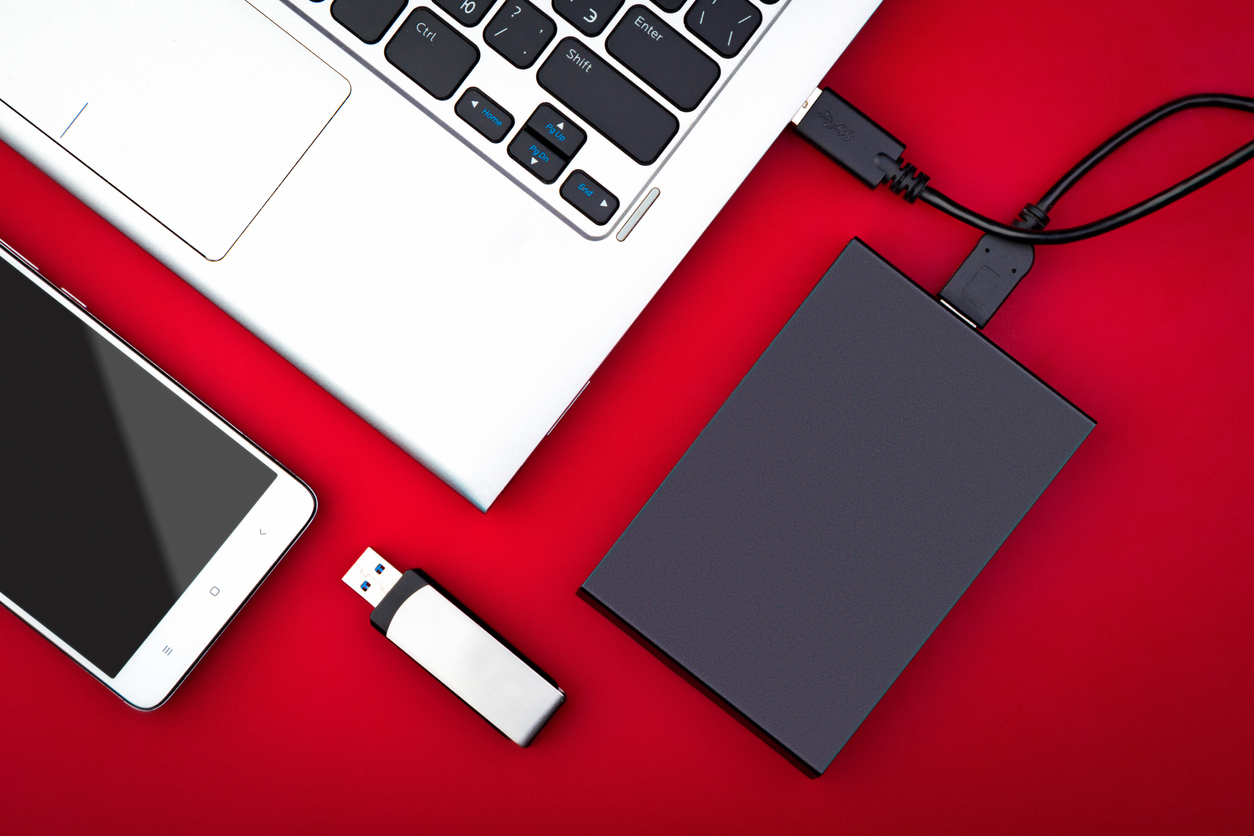 Overhead view of laptop with external hard drive plugged in and a USB thumb drive.