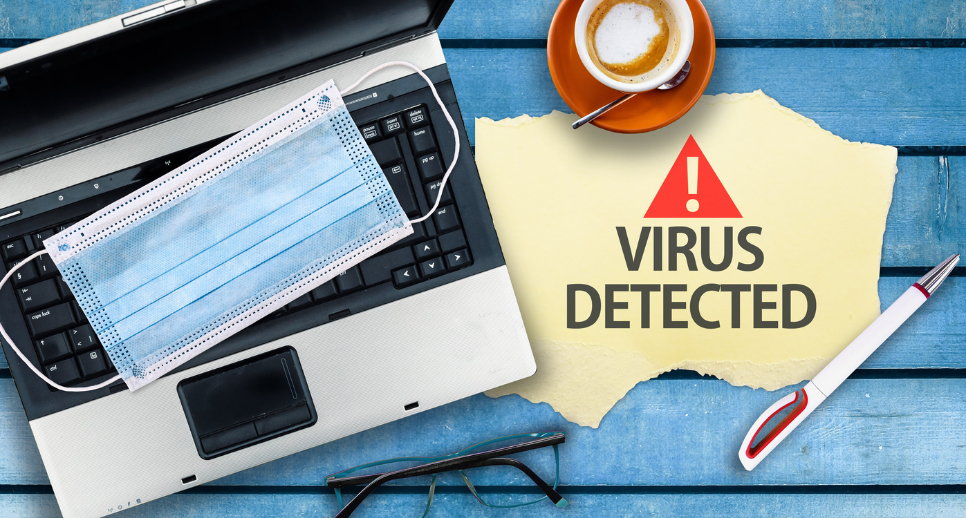 A sign saying Virus Detected next to a laptop with a surgical mask on the keyboard.