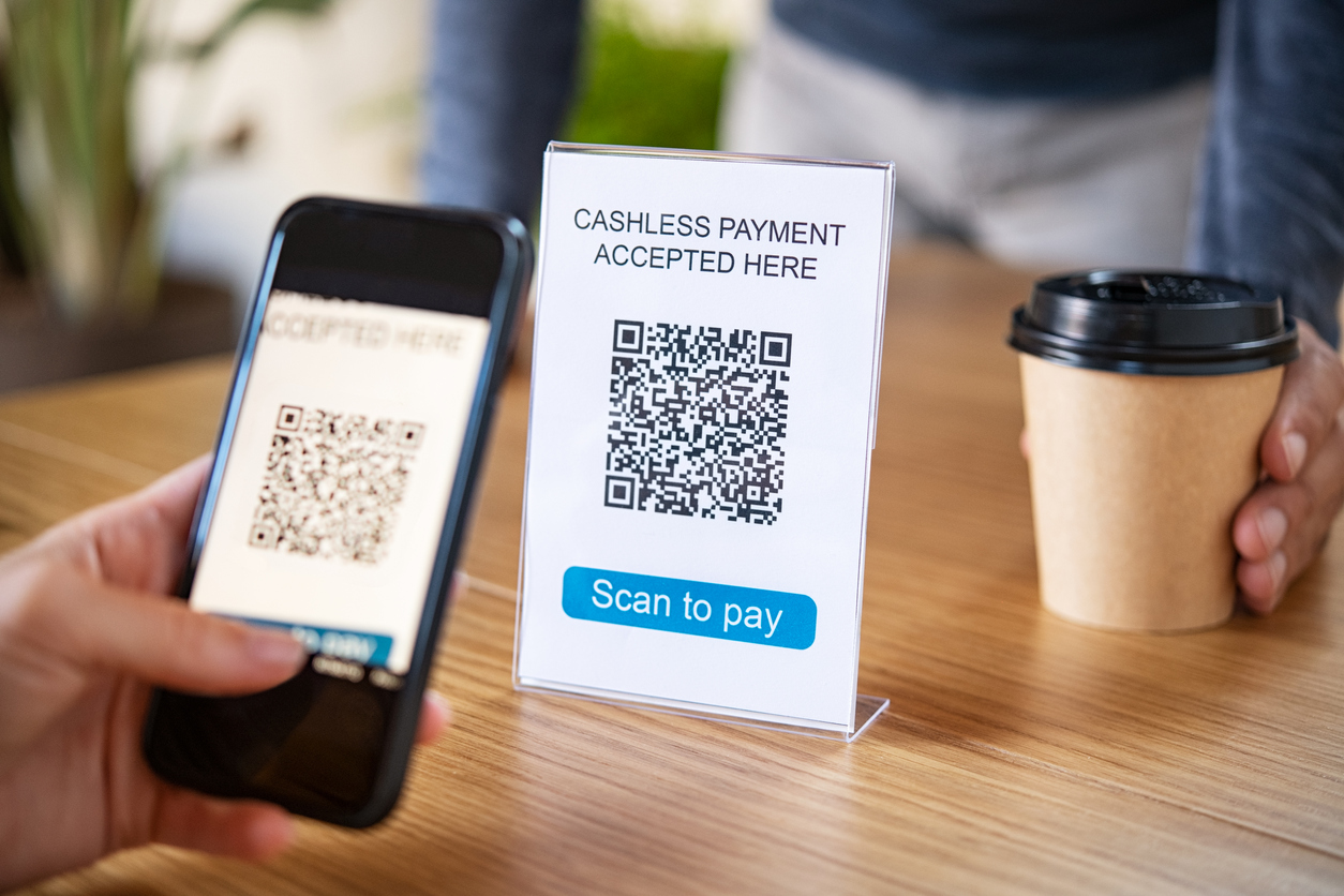 A customer scans a QR code to pay for coffee without contact.