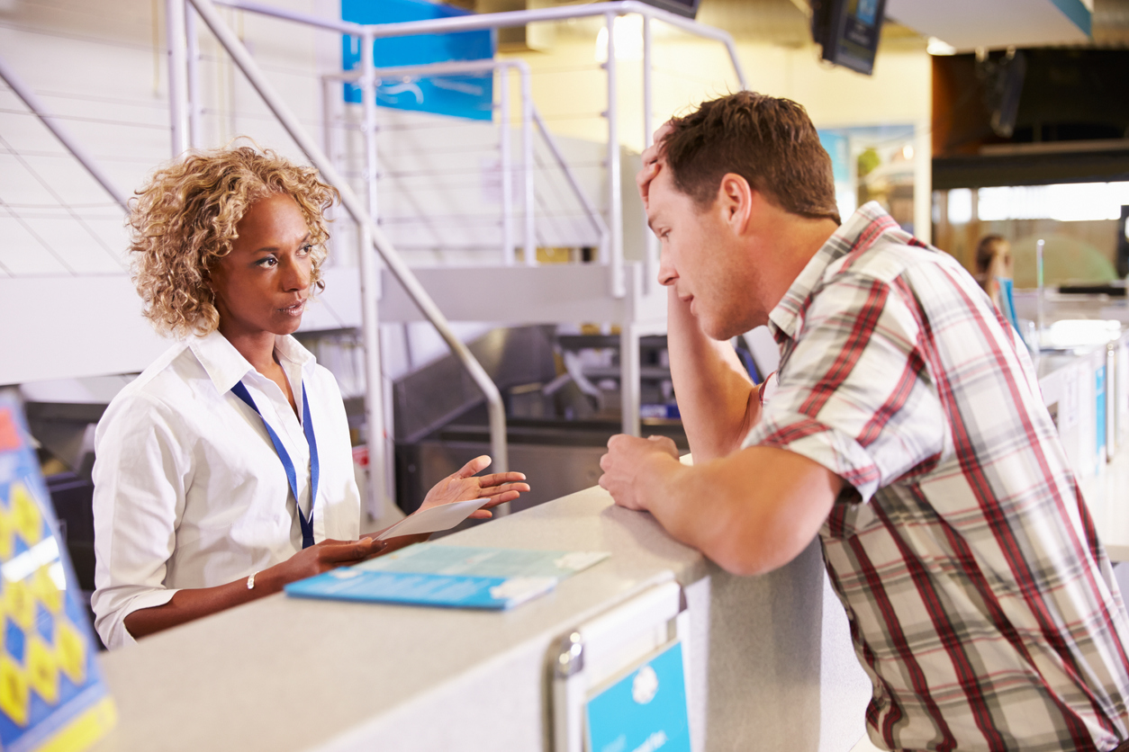 A frustrated traveler talks to an airline employee at the desk.