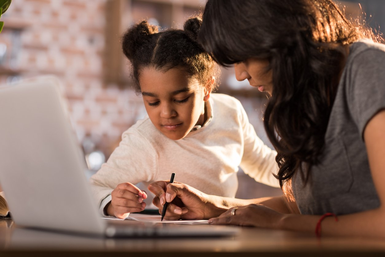 A mother helps her young daughter with schoolwork at home with a laptop in the foreground.