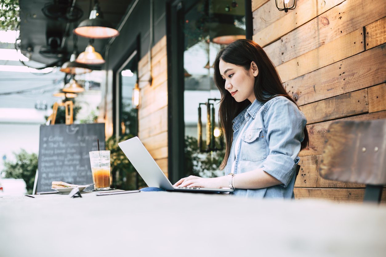 Woman on a laptop outside a coffee shop.