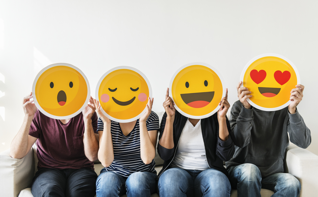 Group of individuals sitting in a row with emoji expression cutouts covering their faces.