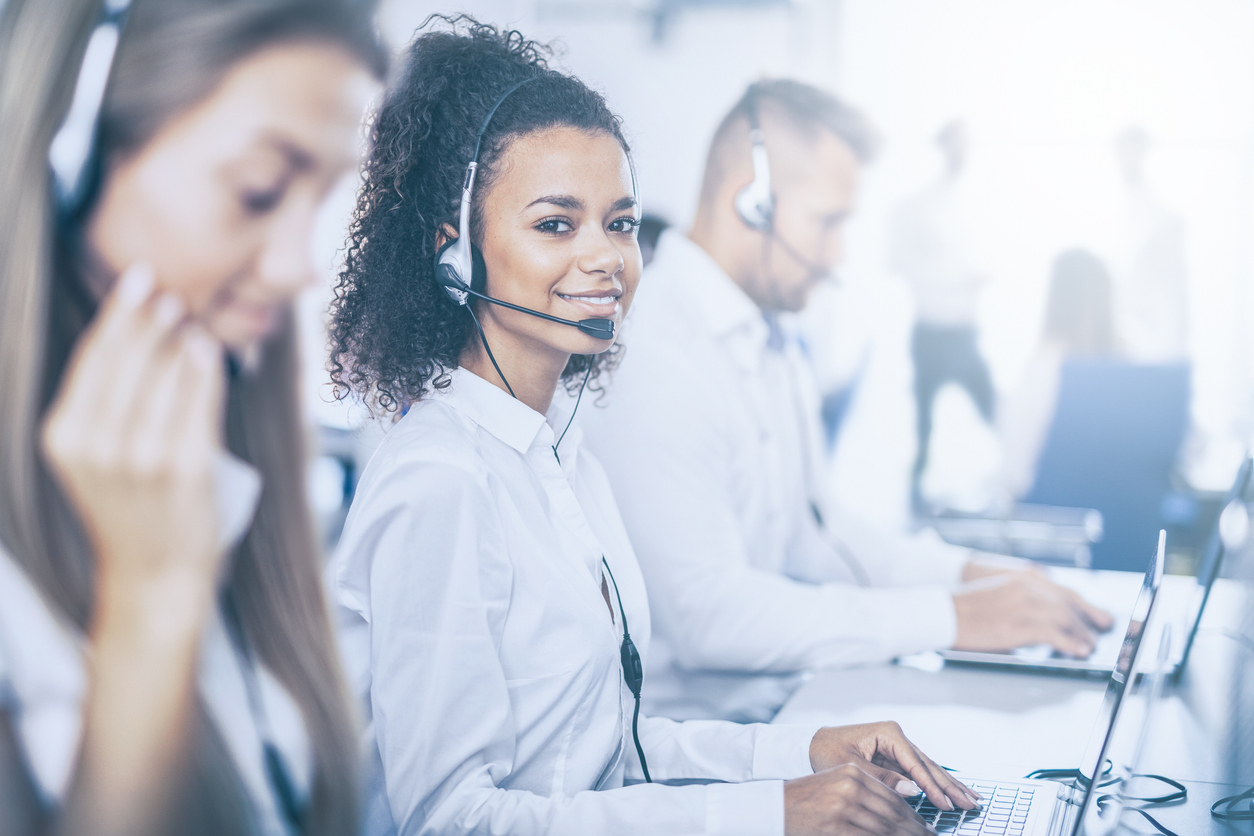Woman wearing headset taking calls in a busy call center.