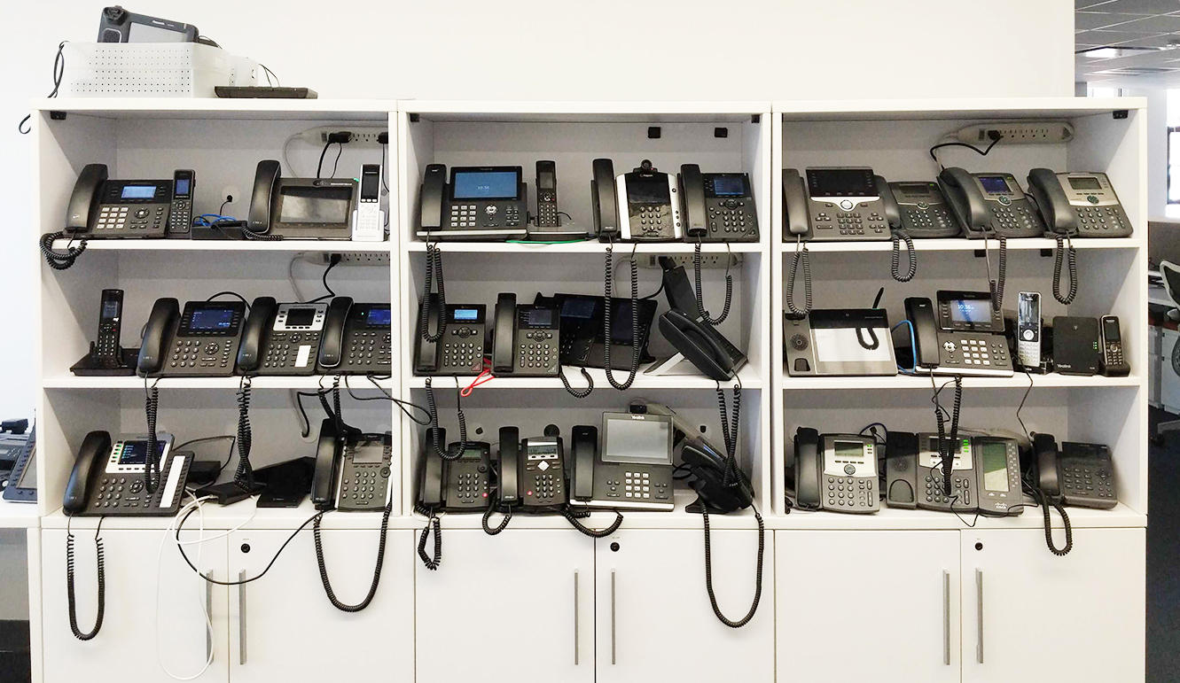 Wall of VoIP desk phones at OnSIP HQ.