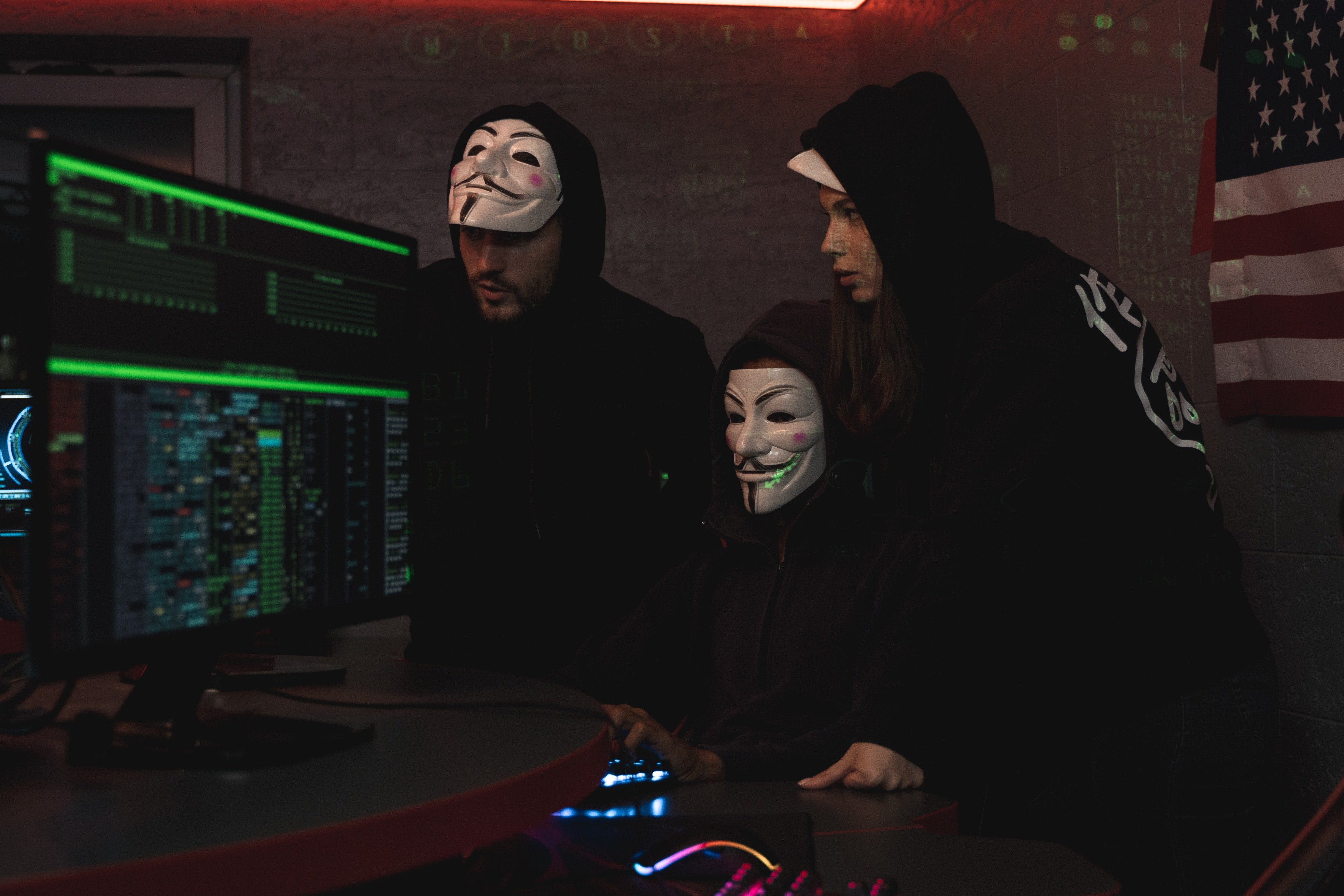 Hackers in V masks look at a monitor together.