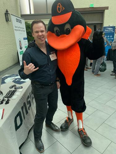 Mike Curtin posing with the Baltimore Orioles Bird mascot.