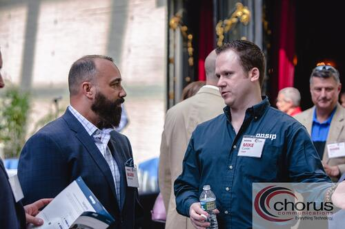 Mark Recene (left), CIO of HS Technology Group, speaks to Mike Curtin (right).