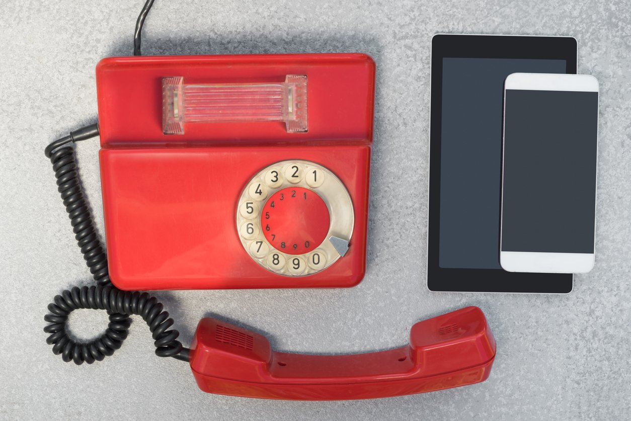 Old red rotary phone sitting next to a tablet and smartphone.