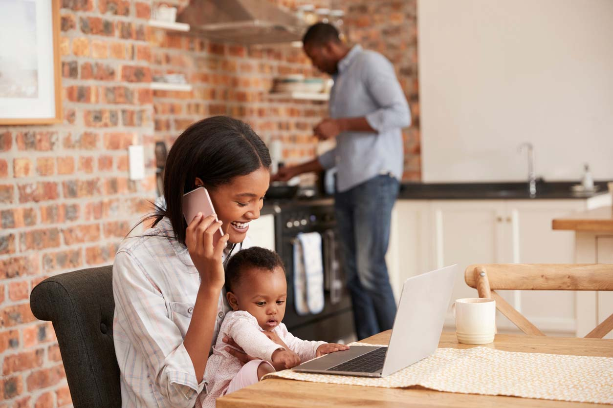 Woman on the phone with a baby in her lap, working remotely at her kitchen table.
